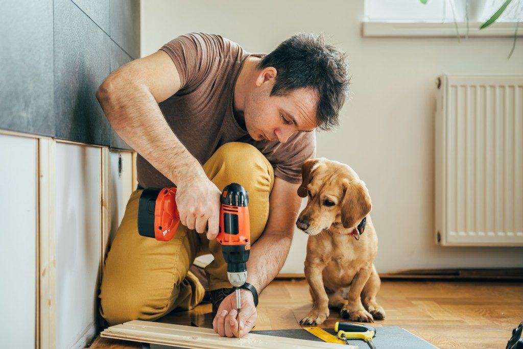 man drilling a plank of wood beside his dog