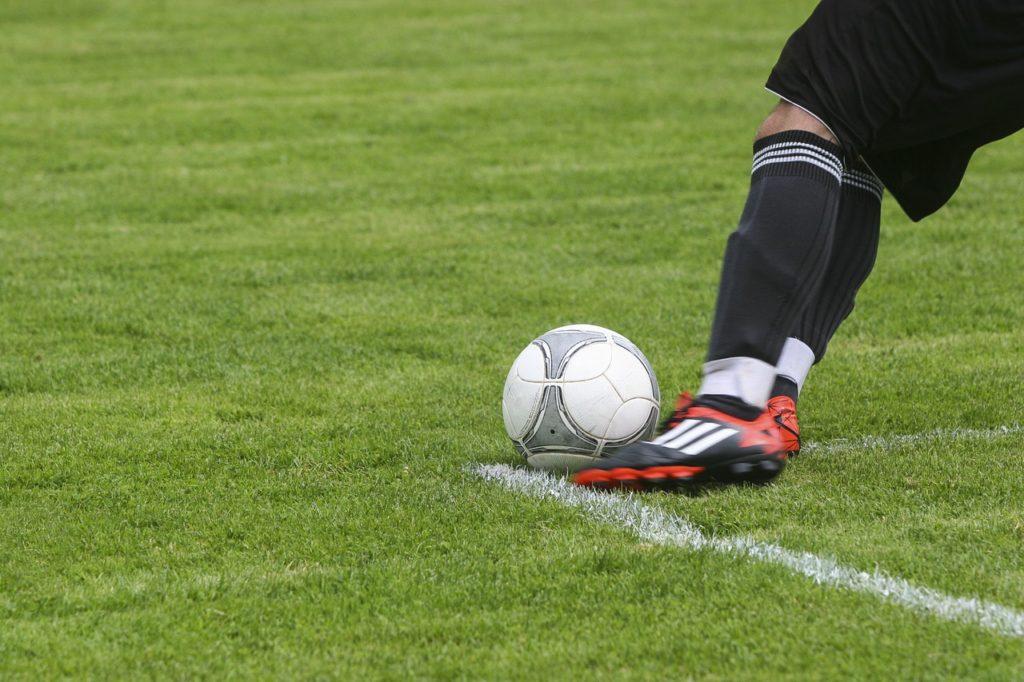 player kicking football