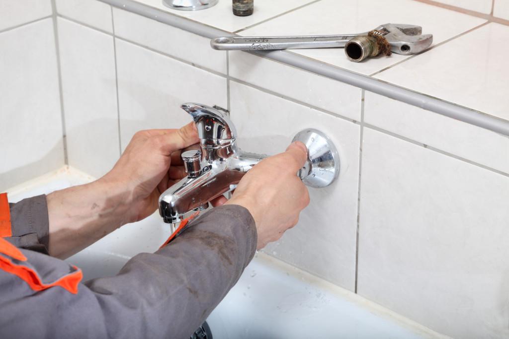 man fixing sink faucet